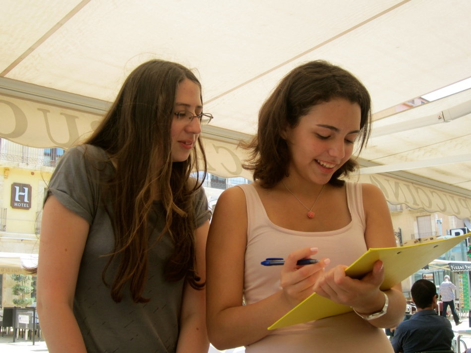 School girls practicing their English with a questionnaire.
